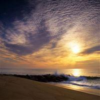 Sun sky clouds sea waves stones breakwater iPad wallpaper