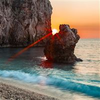 Sun beams rocks block progal sea coast stones wave iPad Pro wallpaper