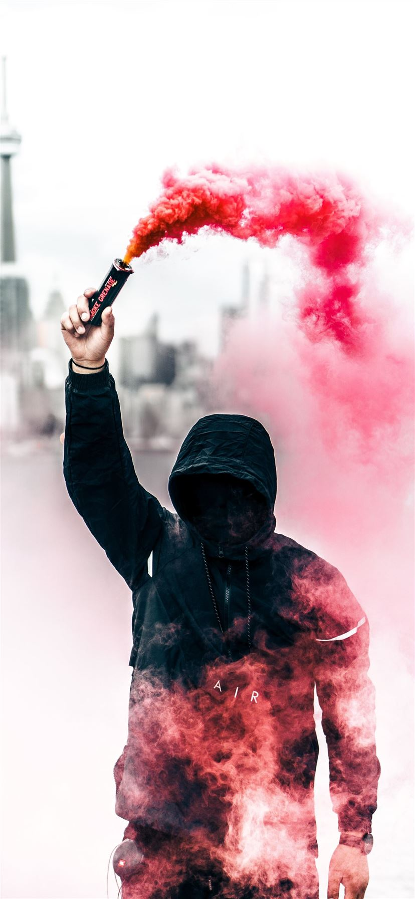 person wearing black and red hoodie holding smoke ... iPhone 11 wallpaper