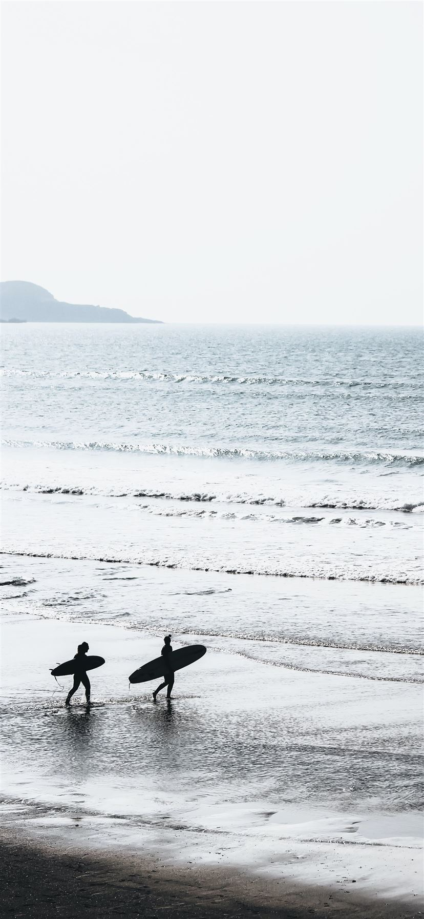 two people carrying surfboards at beach during day... iPhone 11 wallpaper