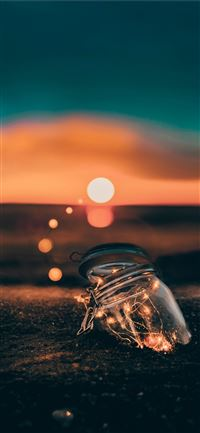 clear glass jar on sand iPhone 11 wallpaper