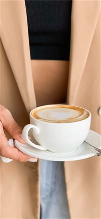 person holding white ceramic cup filled with coffe... iPhone 11 wallpaper