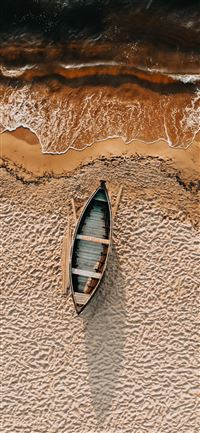 brown and white boat on brown sand iPhone 11 wallpaper