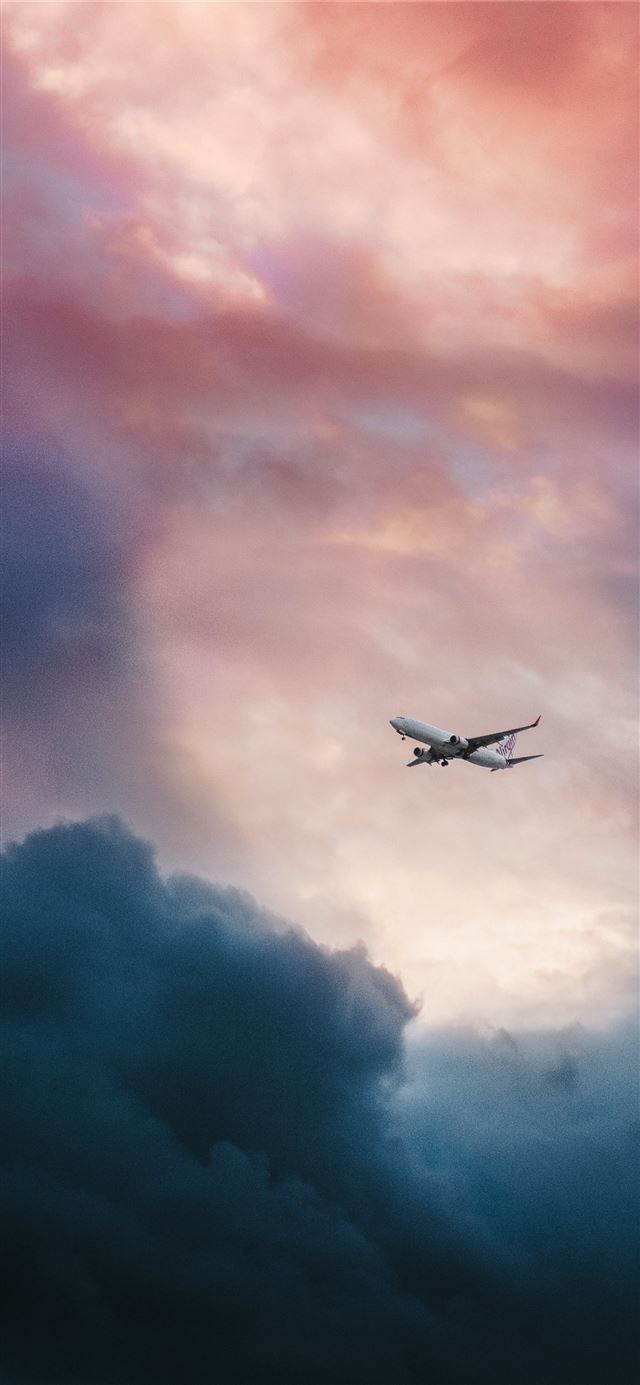 white plane flying over gray clouds iPhone 12 wallpaper