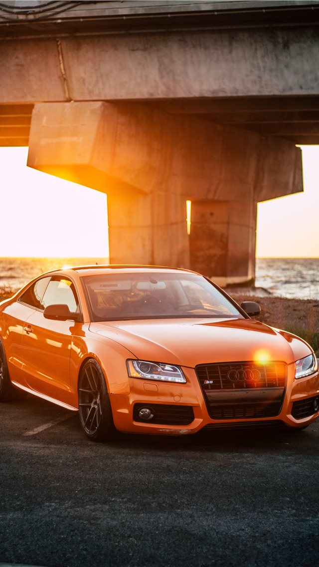 orange Audi coupe parked on gray concrete road iPhone wallpaper
