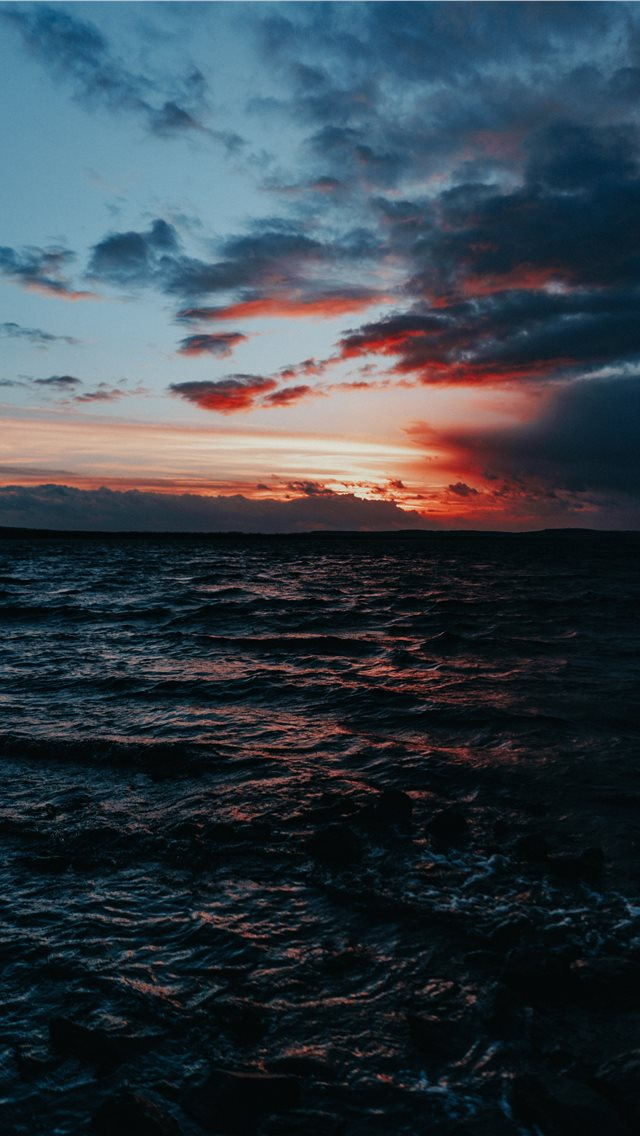 body of water under grey sky iPhone wallpaper