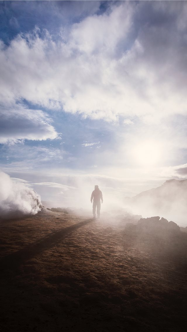 person standing near the edge of a mountain near c... iPhone wallpaper