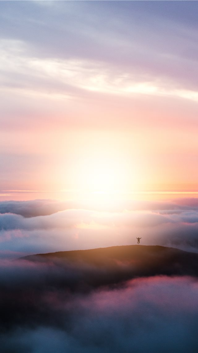 man jumping on hill during golden hour iPhone wallpaper