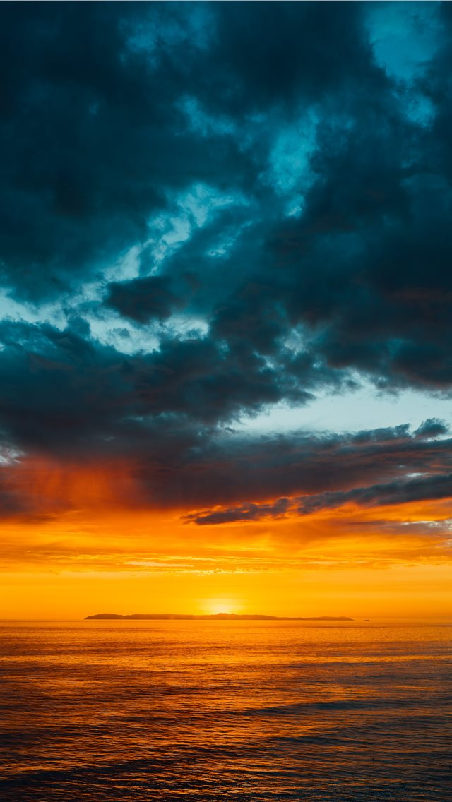 green and black clouds partly covering orange sky ... iPhone wallpaper