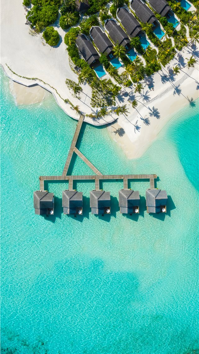 brown huts on body of water in aerial photography iPhone wallpaper