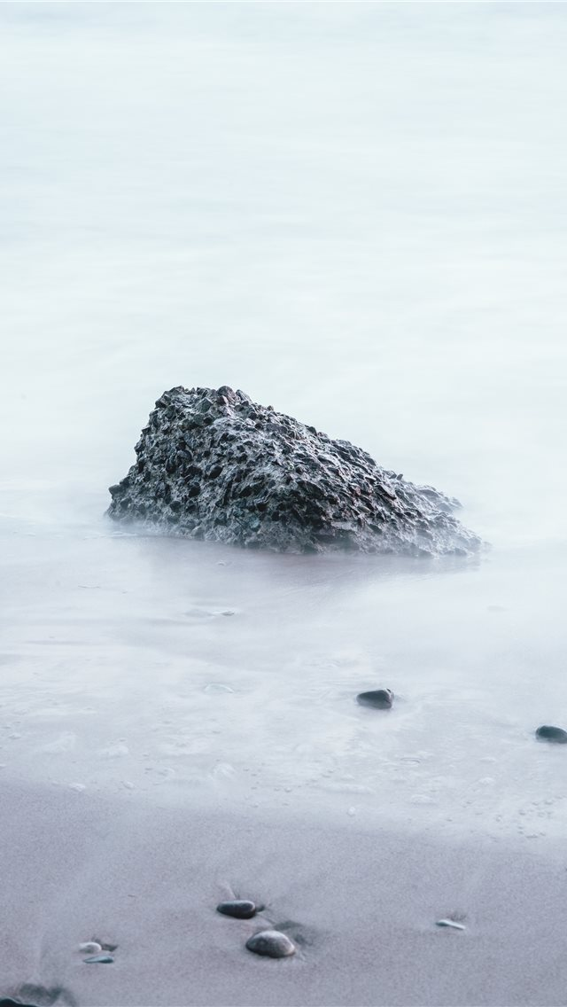 rock on sand shore during day iPhone wallpaper