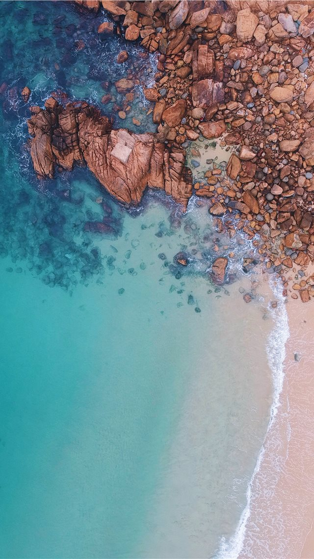 aerial view of rocks near body of water iPhone wallpaper
