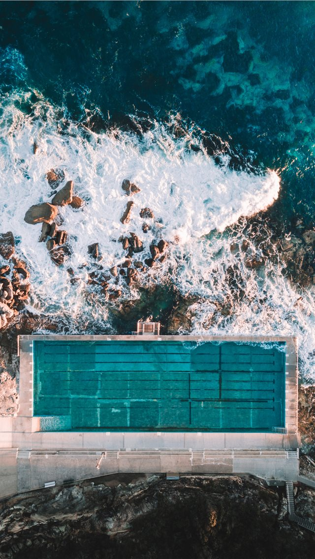 aerial photo of concrete building near sea iPhone wallpaper