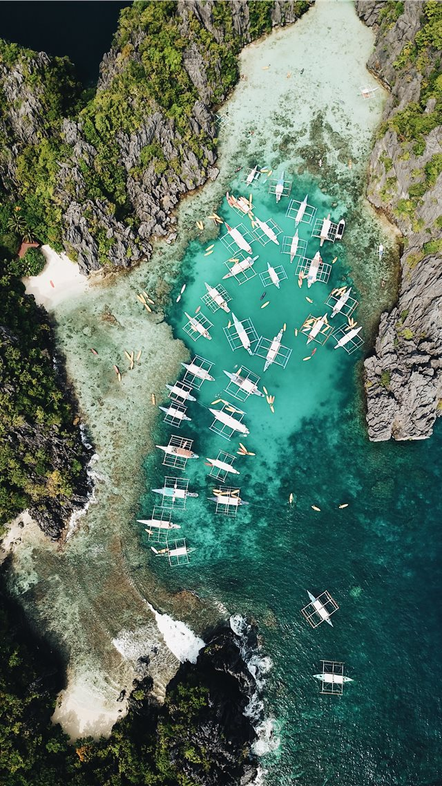 aerial photography of boats beside mountain during... iPhone wallpaper