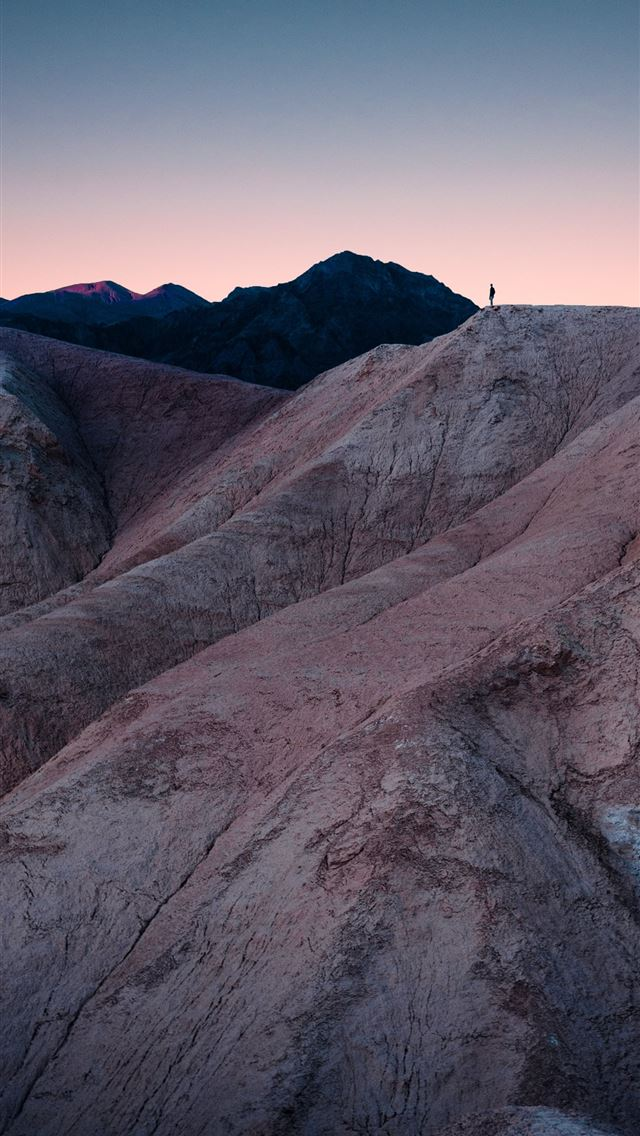 man standing on mountain during daytime iPhone wallpaper