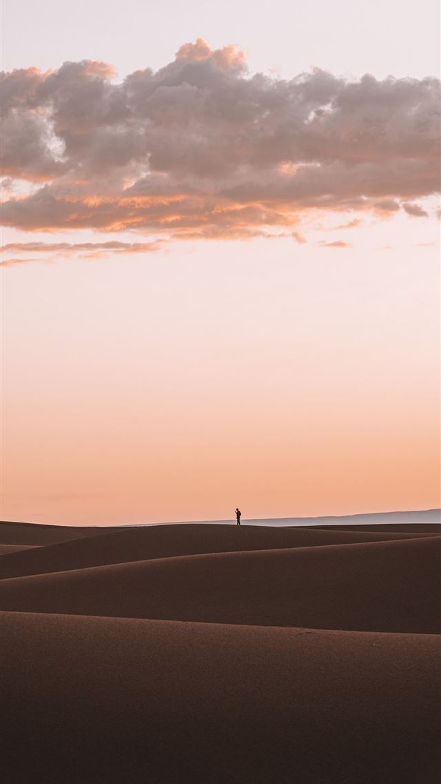 silhouette of person standing on desert iPhone wallpaper