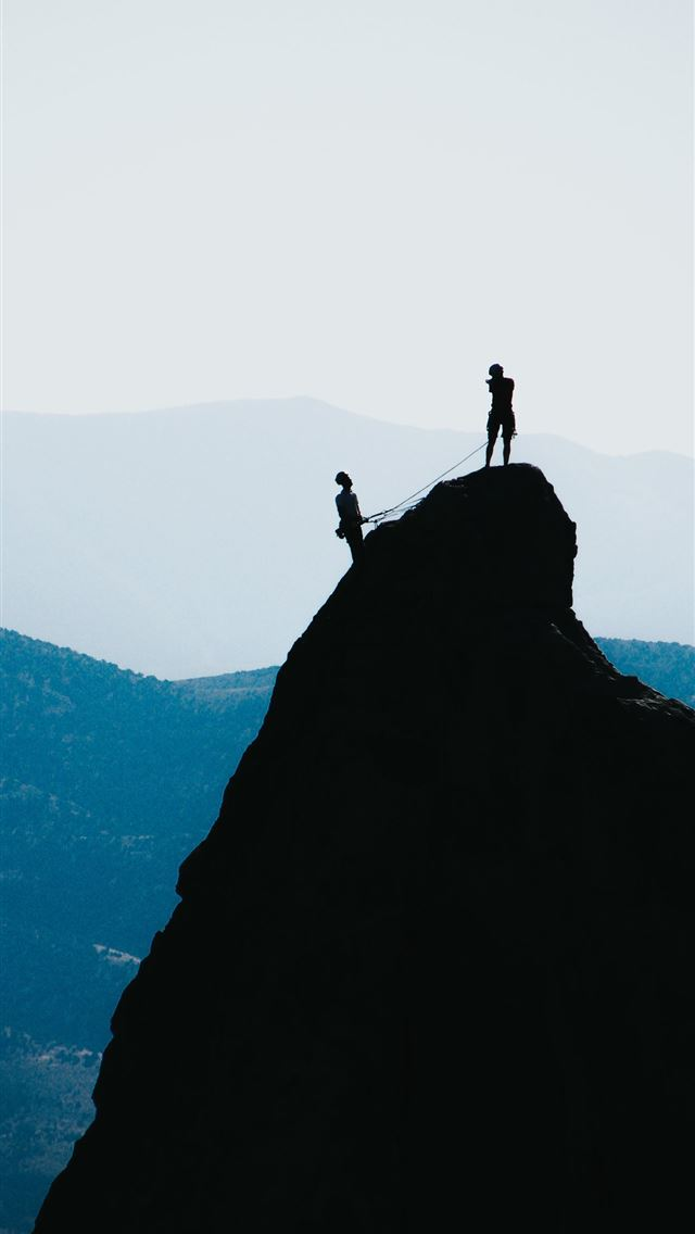 silhouette of two people standing on mountain duri... iPhone wallpaper