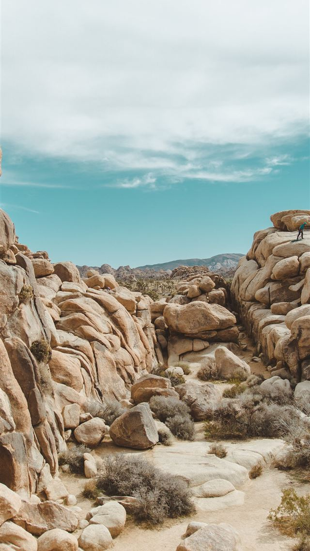 gray rocks under cloudy sky iPhone wallpaper