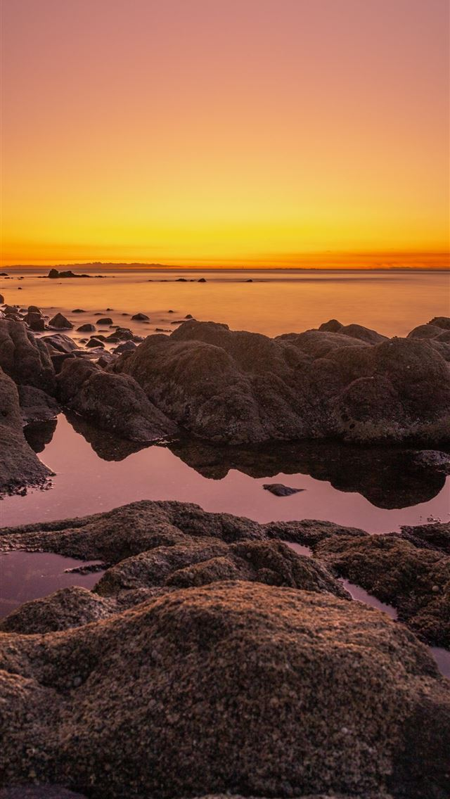 rocky shore during sunset with orange sky iPhone wallpaper