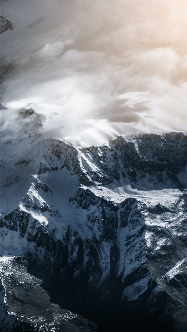 snow covered mountain under cloudy sky during dayt... iPhone wallpaper