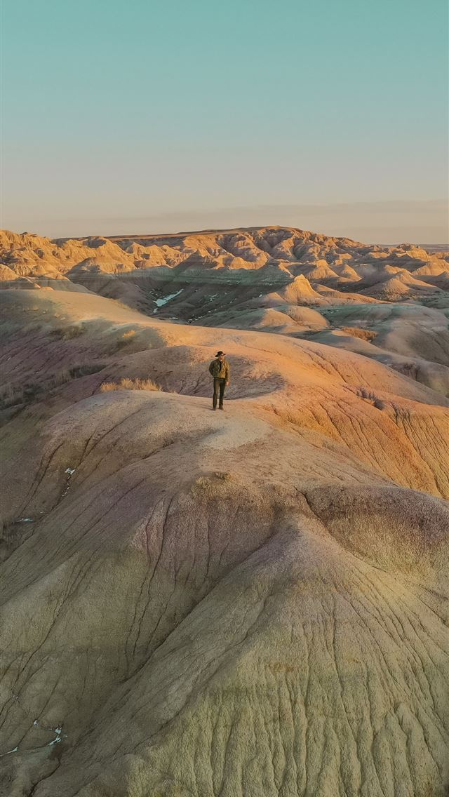 person standing on brown rock formation during day... iPhone wallpaper