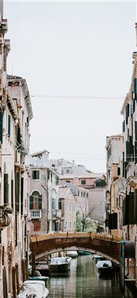 Laundry hanging over Venetian canal and bridge iPhone X wallpaper