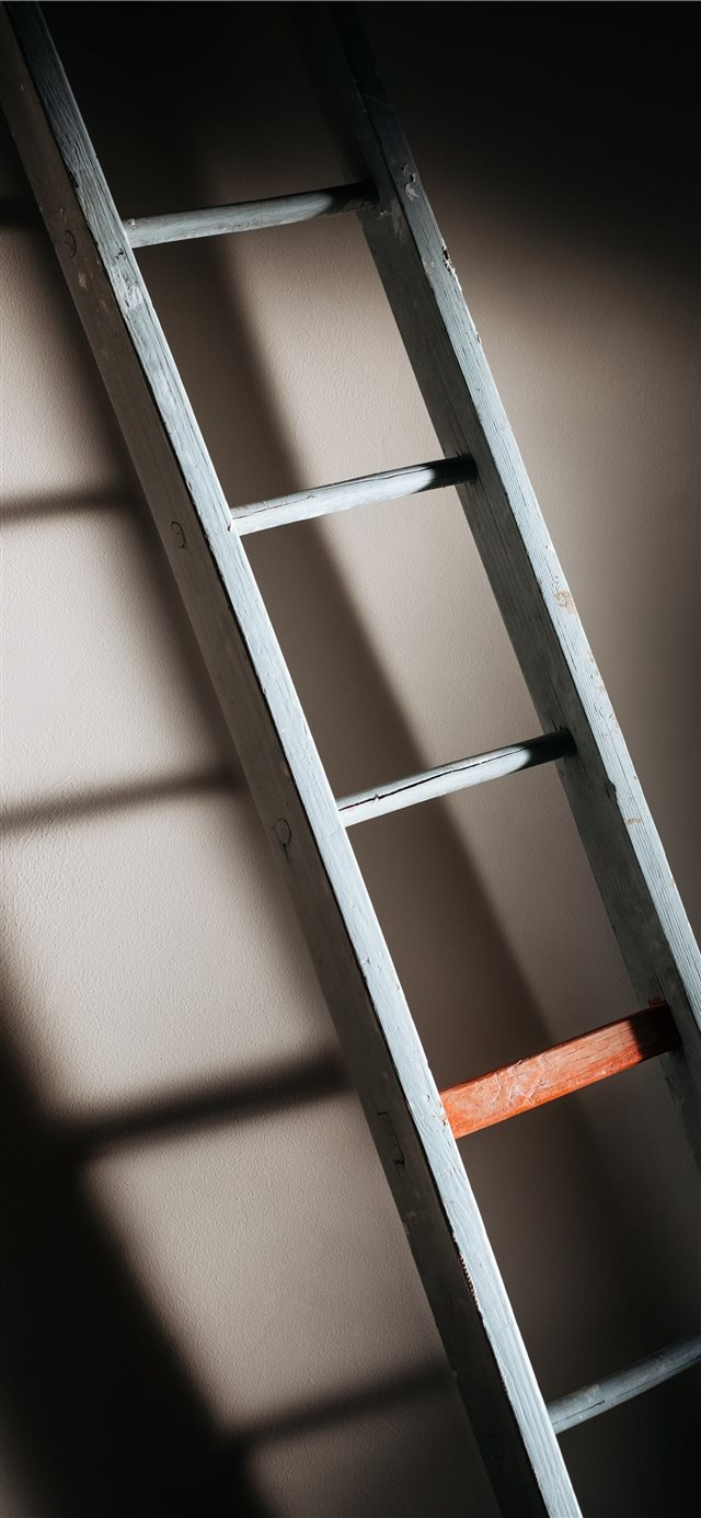 An old wooden ladder casting soft shadows on wall iPhone 11 wallpaper