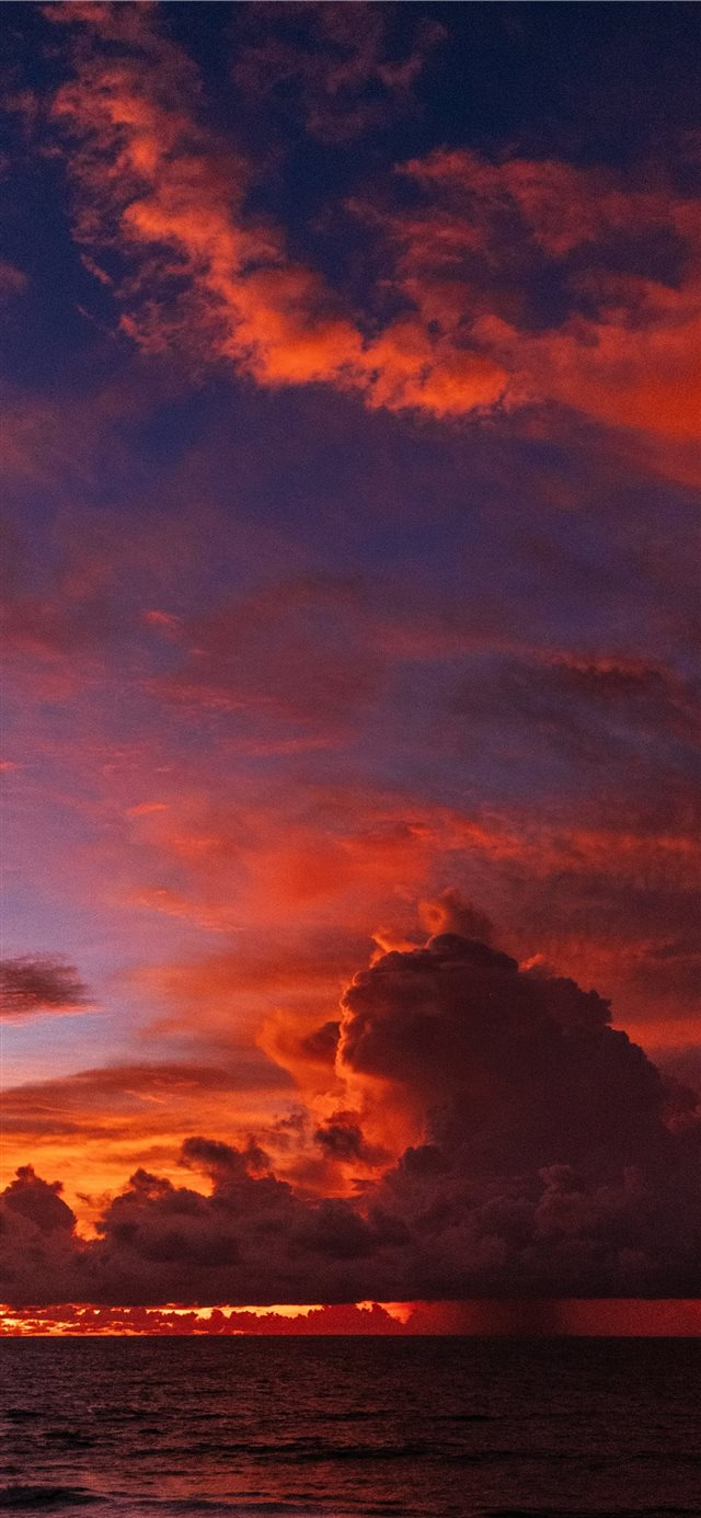 ocean under orange colored clouds iPhone 11 wallpaper