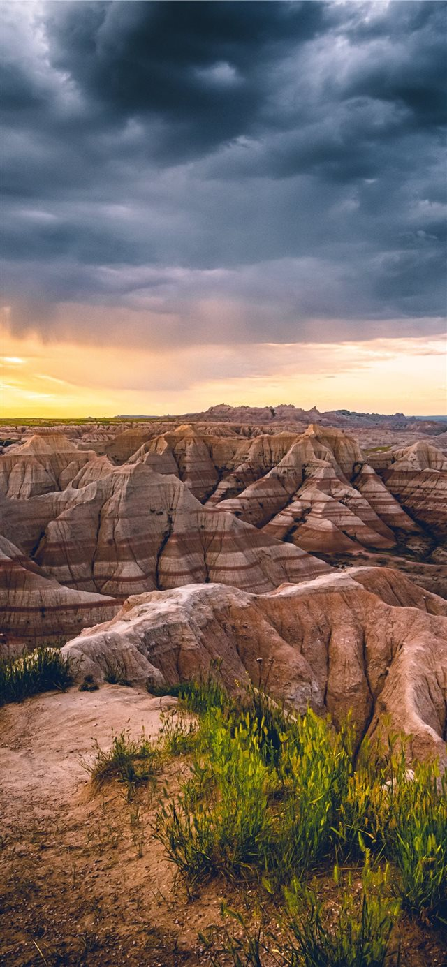 A morning storm in the Badlands being chased away ... iPhone X wallpaper