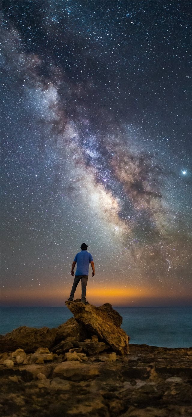 man standing on rock facing ocean under starry nig... iPhone X wallpaper