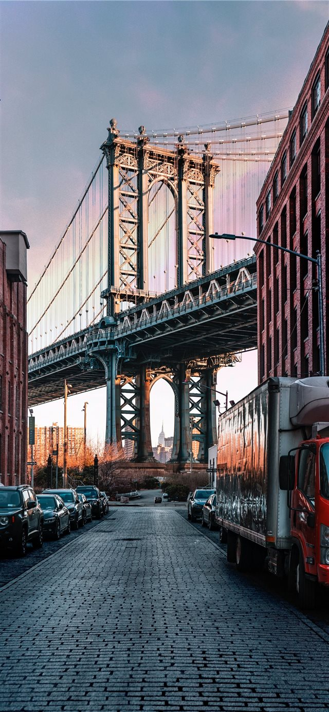 cars parked on both sides of street near bridge iPhone X wallpaper