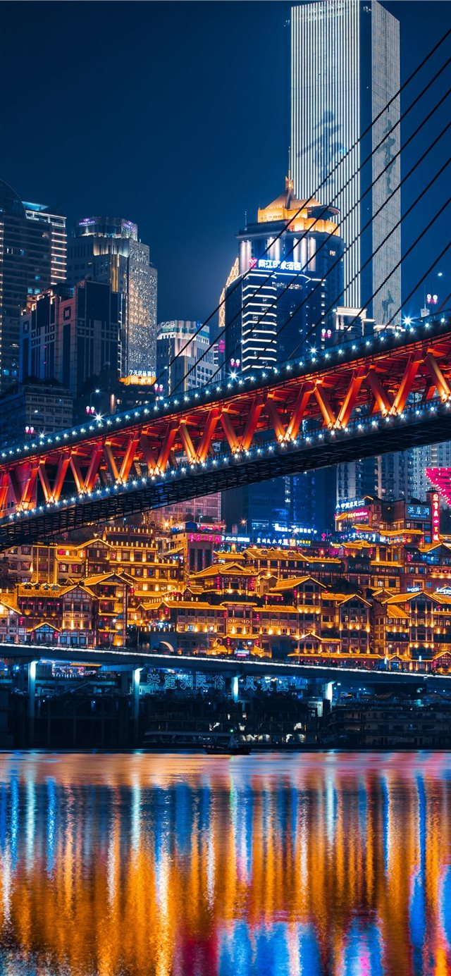 lighted bridge across calm water iPhone 11 wallpaper