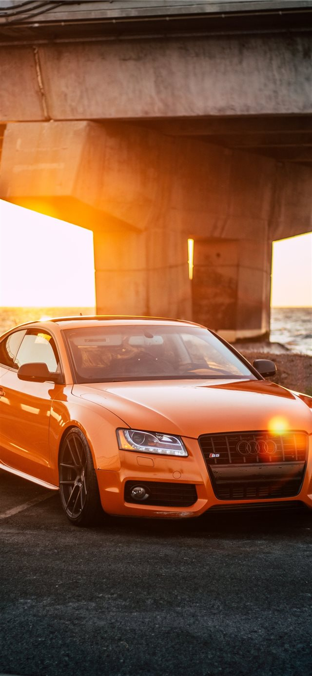 orange Audi coupe parked on gray concrete road iPhone X wallpaper