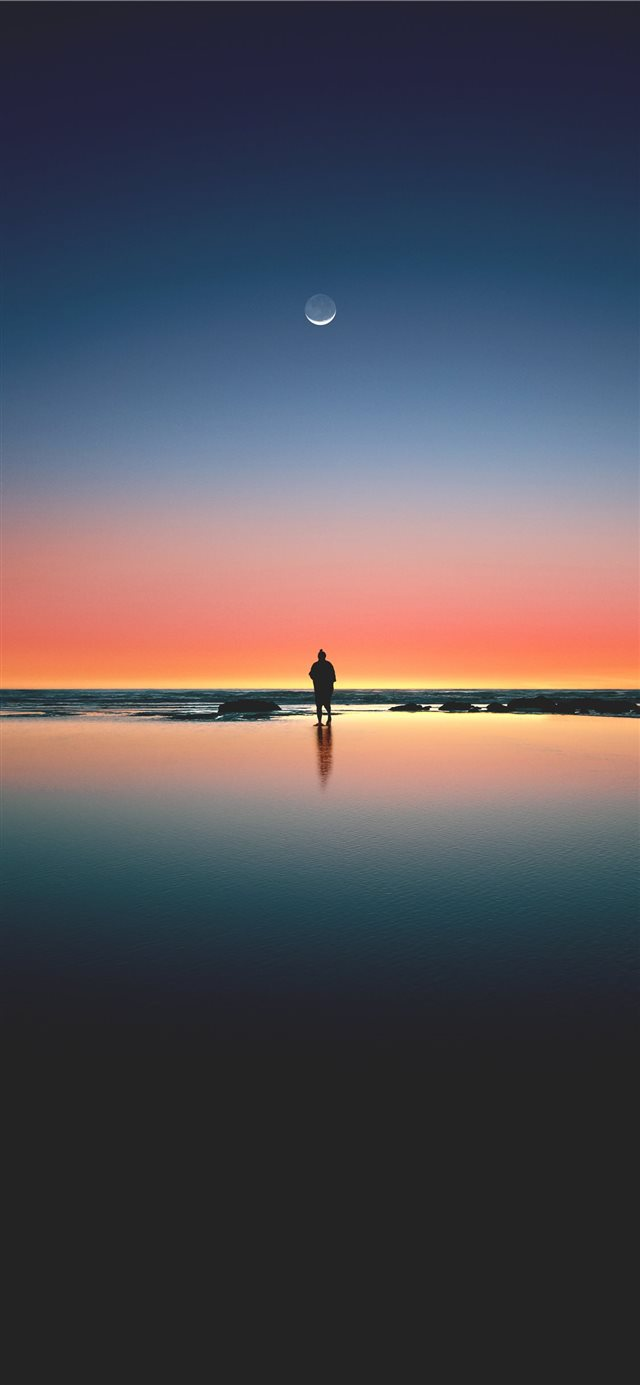 silhouette of man standing on seashore iPhone 11 wallpaper