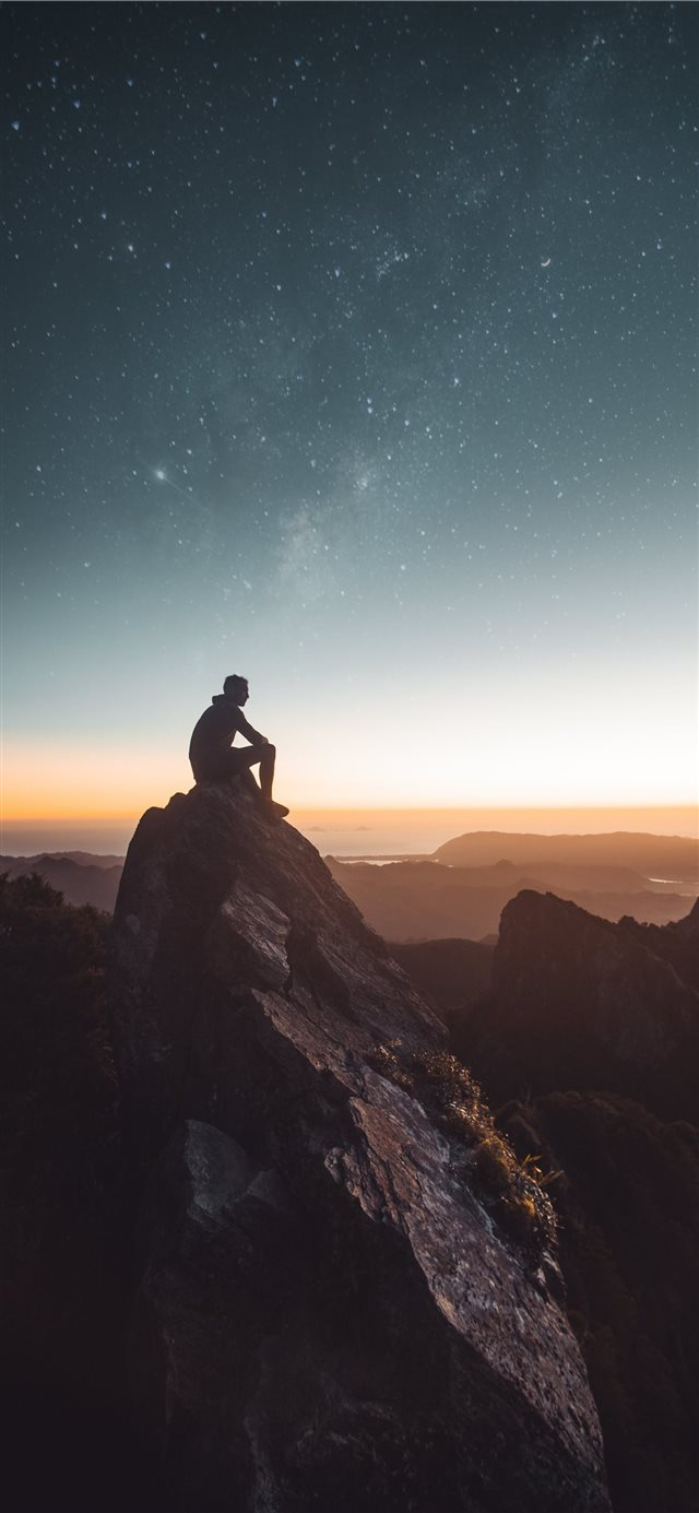 silhouette of person sitting on rock formation dur... iPhone 11 wallpaper