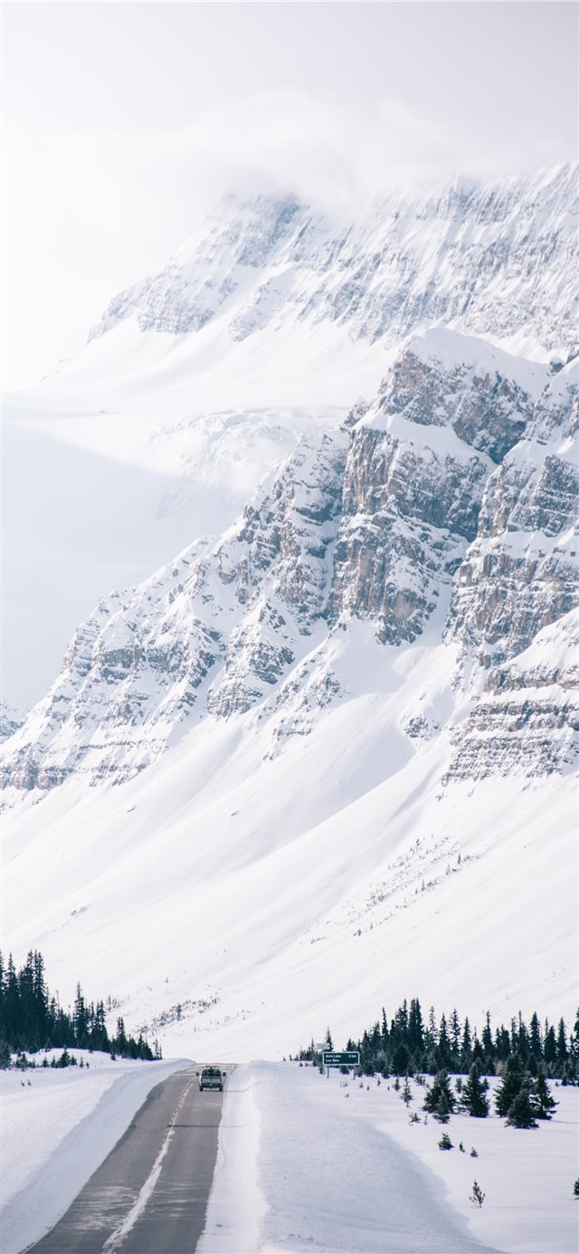 white snow covered hills and road side iPhone X wallpaper
