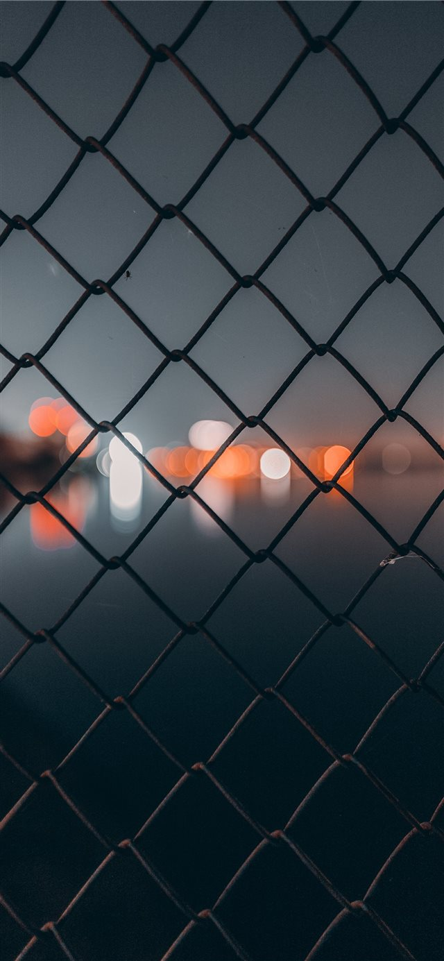 chain link fence behind bokeh iPhone X wallpaper