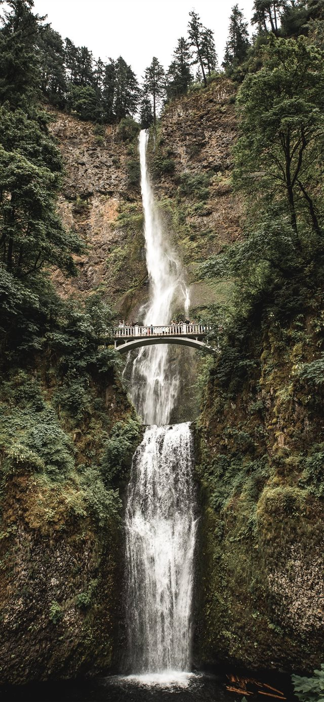 gray bridge in the middle of falls iPhone X wallpaper