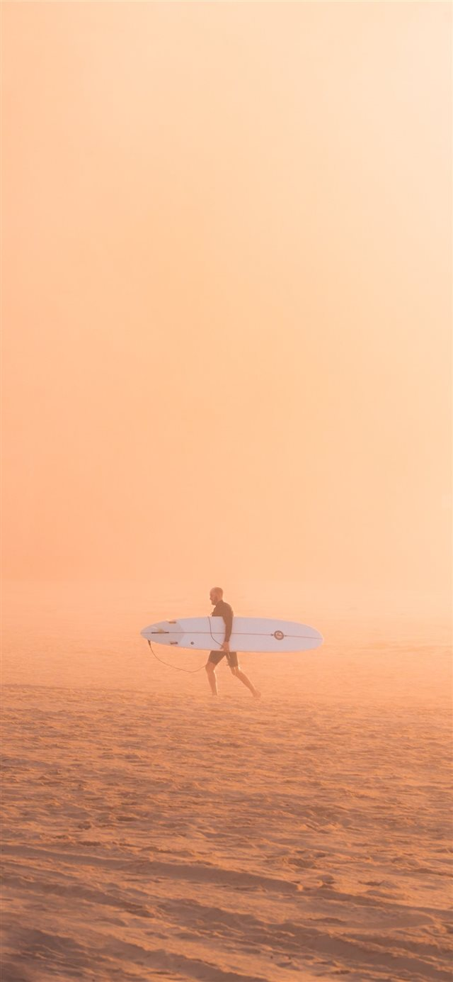 man carrying surfboard iPhone X wallpaper
