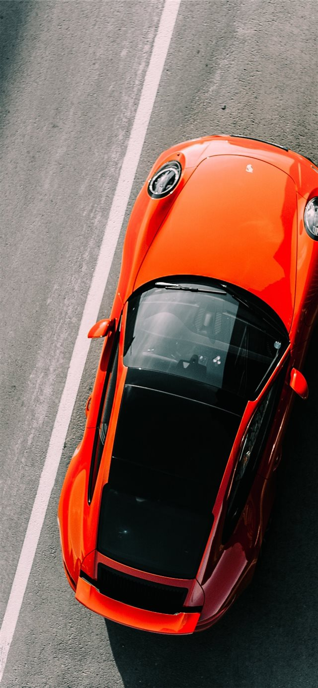 orange vehicle on road close up photography iPhone X wallpaper
