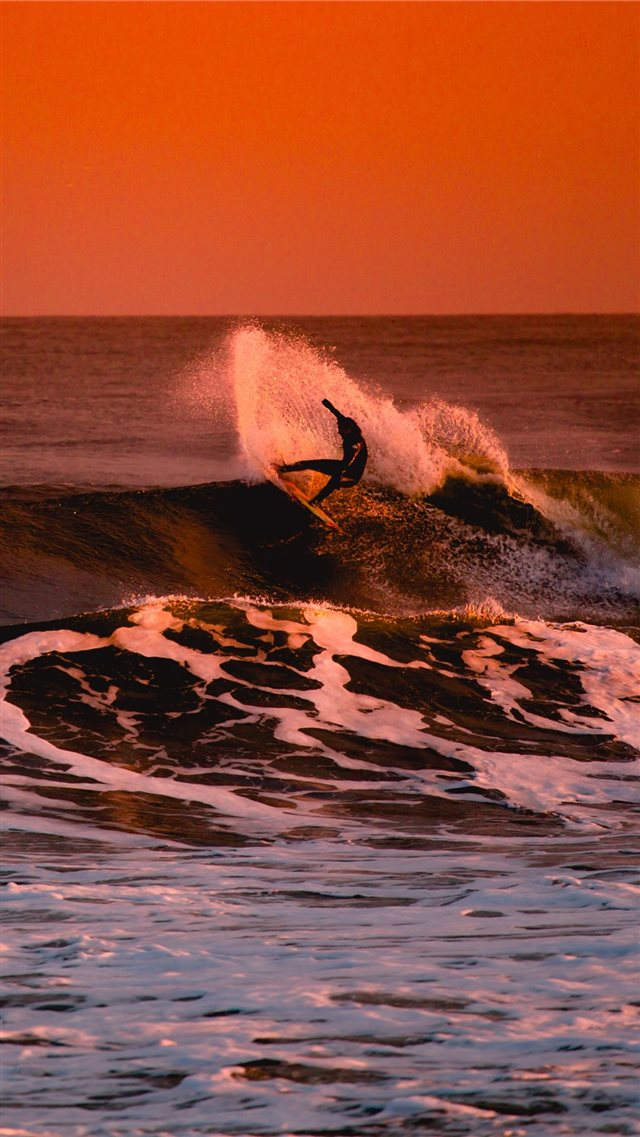 person surfing during sunset iPhone SE wallpaper