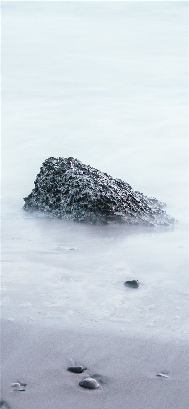 rock on sand shore during day iPhone X wallpaper