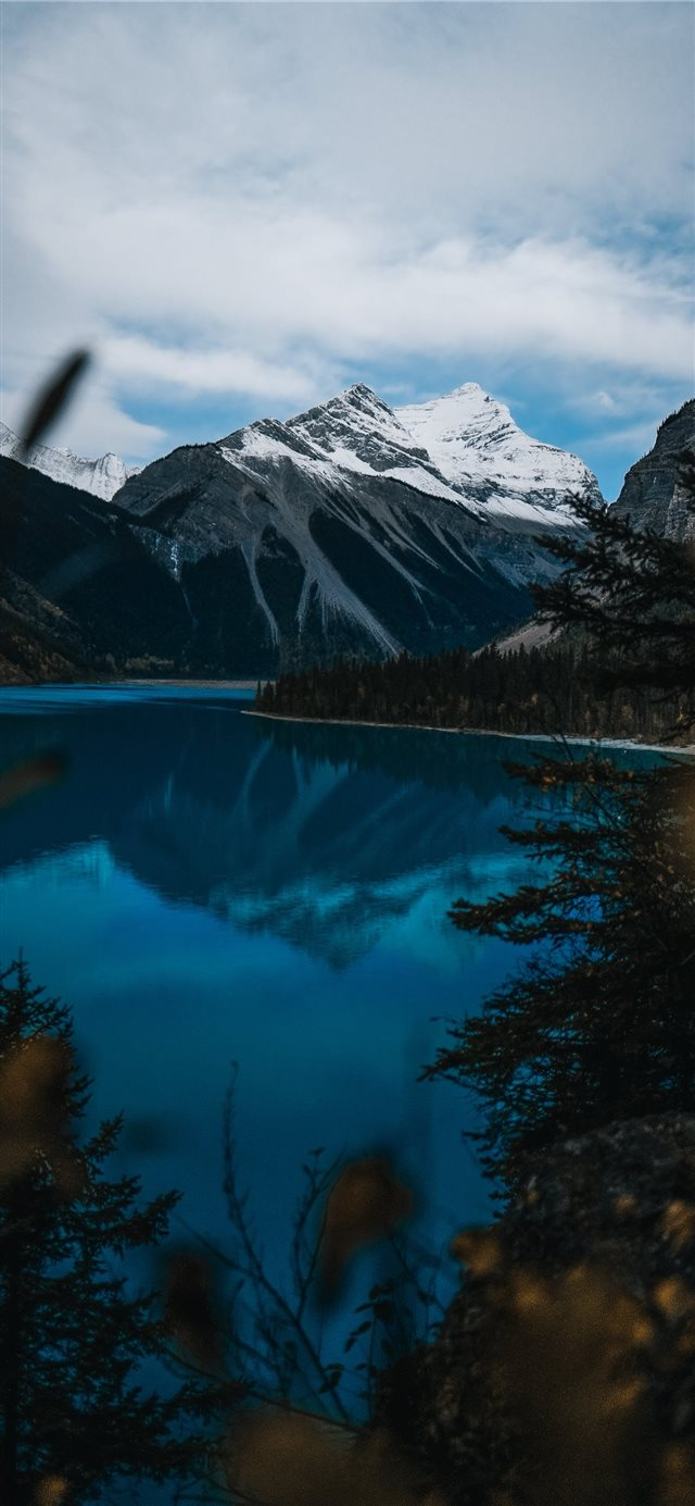 body of water near snow covered mountain during da... iPhone 11 wallpaper