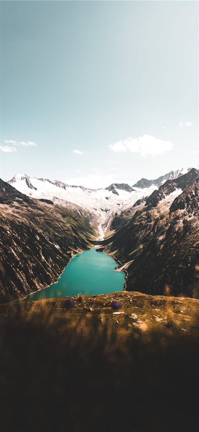 aerial photography of body of water between mounta... iPhone X wallpaper