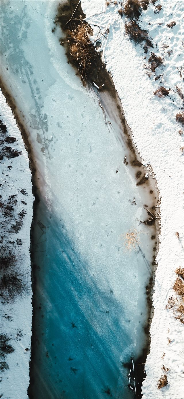 aerial photography of river beside snow field iPhone X wallpaper