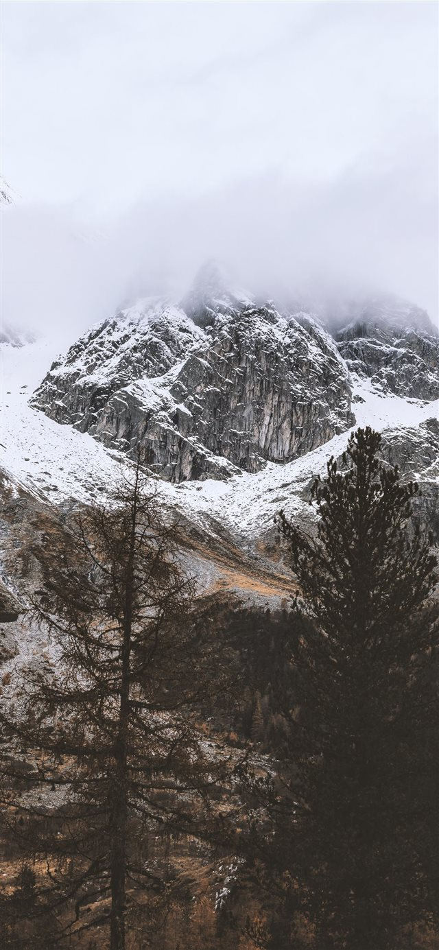 snow capped rocky mountain under cloudy sky iPhone X wallpaper