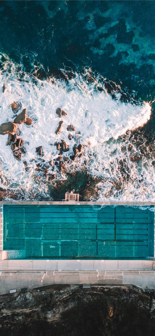 aerial photo of concrete building near sea iPhone X wallpaper