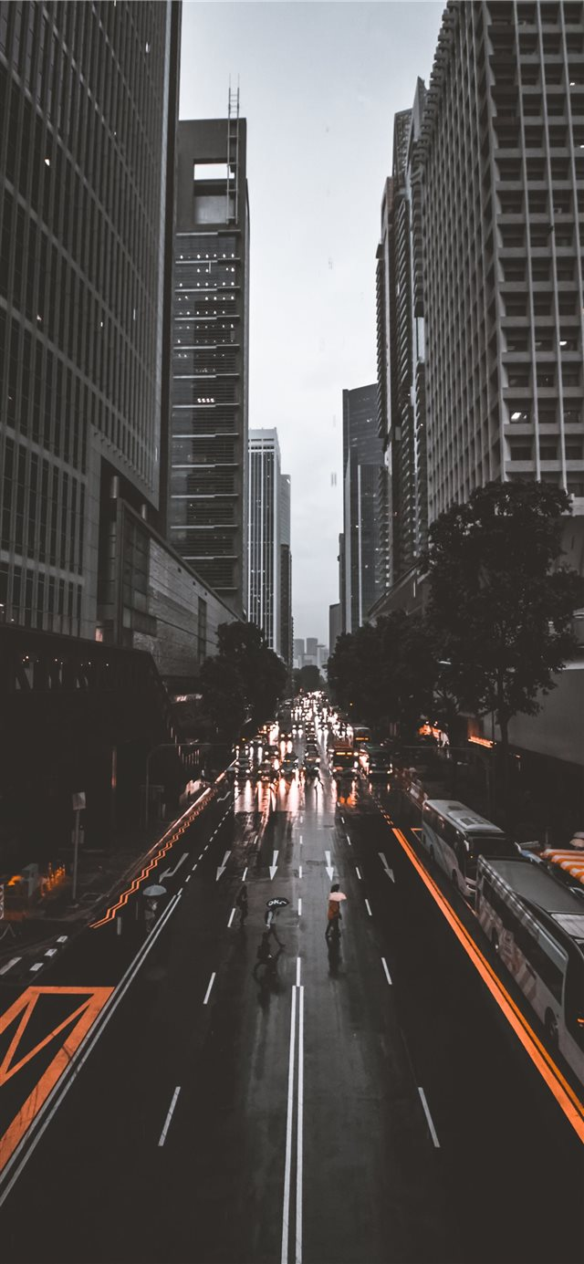 people crossing road between high rise buildings iPhone X wallpaper