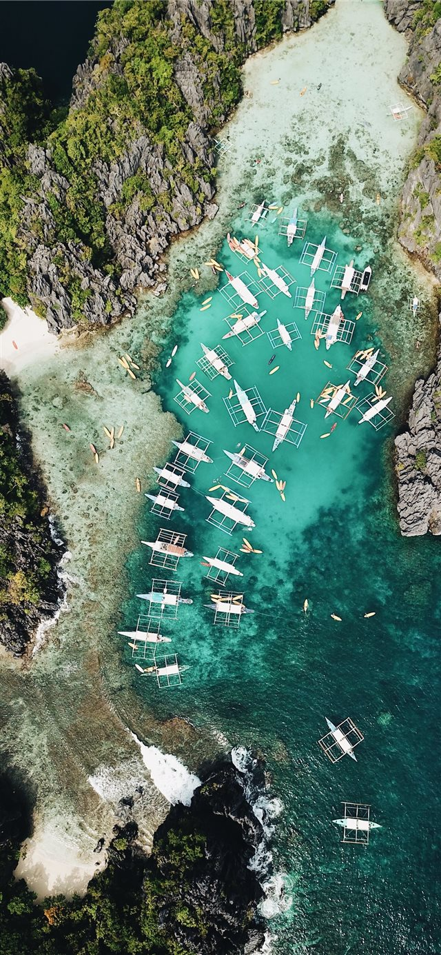 aerial photography of boats beside mountain during... iPhone X wallpaper