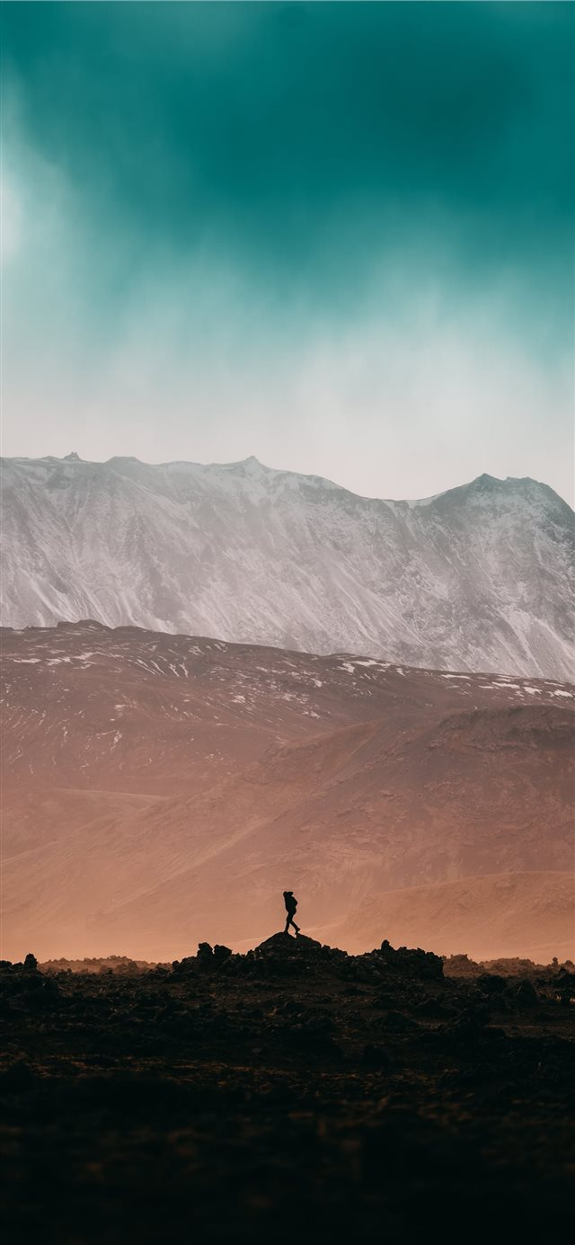 person standing on rock near snow covered mountain... iPhone X wallpaper